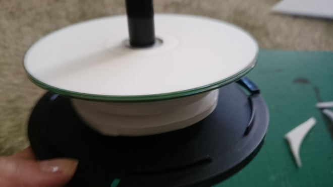 The extra layers added to the spindle and free turning CD on the top which would spin against the one of the base